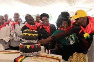 President Robert Mugabe (center l.), his wife Grace, daughter Bona, and her fiance Sam Chikoore cut his birthday cake during celebrations to mark his 90th Birthday in Marondera