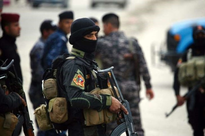 A member of Iraqi security forces stands guard at the site of a suicide attack south of the capital Baghdad