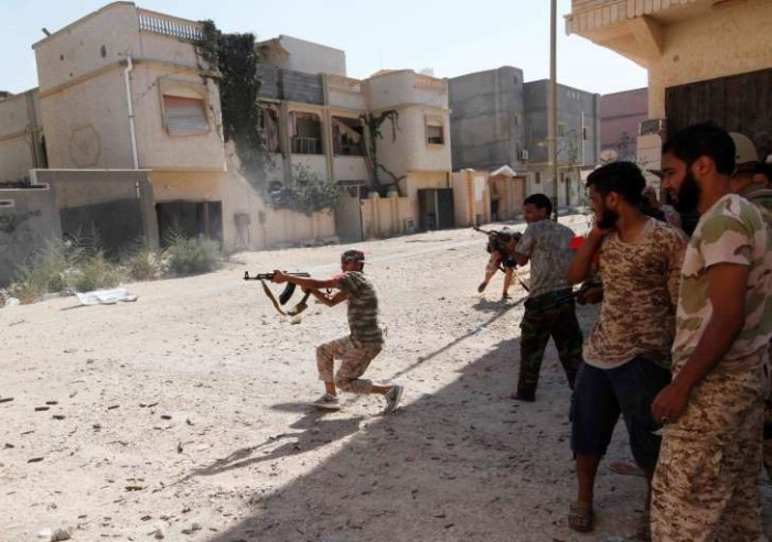 A member of Libyan forces allied with the UN-backed government fires a weapon towards Islamic State militants in neighborhood Number One in central Sirte, Libya
