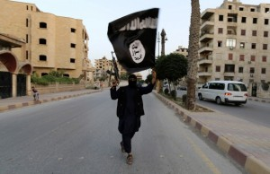 An ISIS member waves the movement's flag in Raqqa, Syria