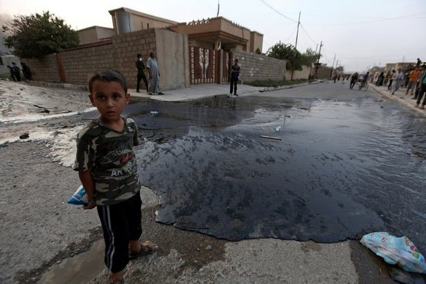 A boy stands near oil spill from wells, set ablaze by Islamic State militants before fleeing the oil-producing region of Qayyara, in Qayyara, Iraq