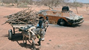 A child leads his wood-filled donkey cart past a destroyed Malian army armored vehicle