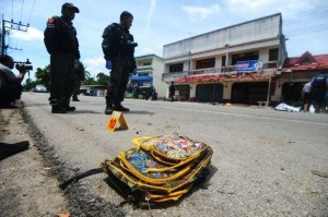 A child's backpack lies on the ground as members of a Thai bomb squad inspect the site of a blast in front of a school by suspected separatist militants in the restive southern province of Narathiwat