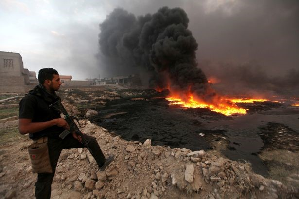 A member of the Iraqi security forces stands with his weapon as fire and smoke rise from oil wells