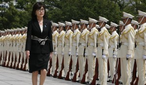 Japan's new Defense Minister Tomomi Inada inspects an honor guard on her first day at the Defense Ministry in Tokyo