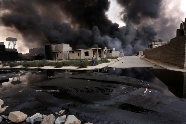 Smoke billows from oil wells, set ablaze by ISIS militants before fleeing the oil-rich region of Qayyarah.