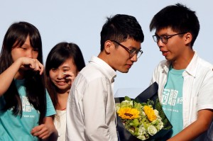 Student leader Joshua Wong (R) greets candidate Nathan Law (2nd R) as supporters share their joy after Law won in the Legislative Council election in Hong Kong.